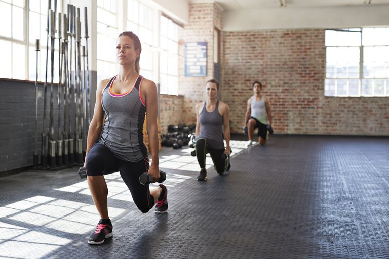 three people doing weighted dumbbell lunge exercise in gym