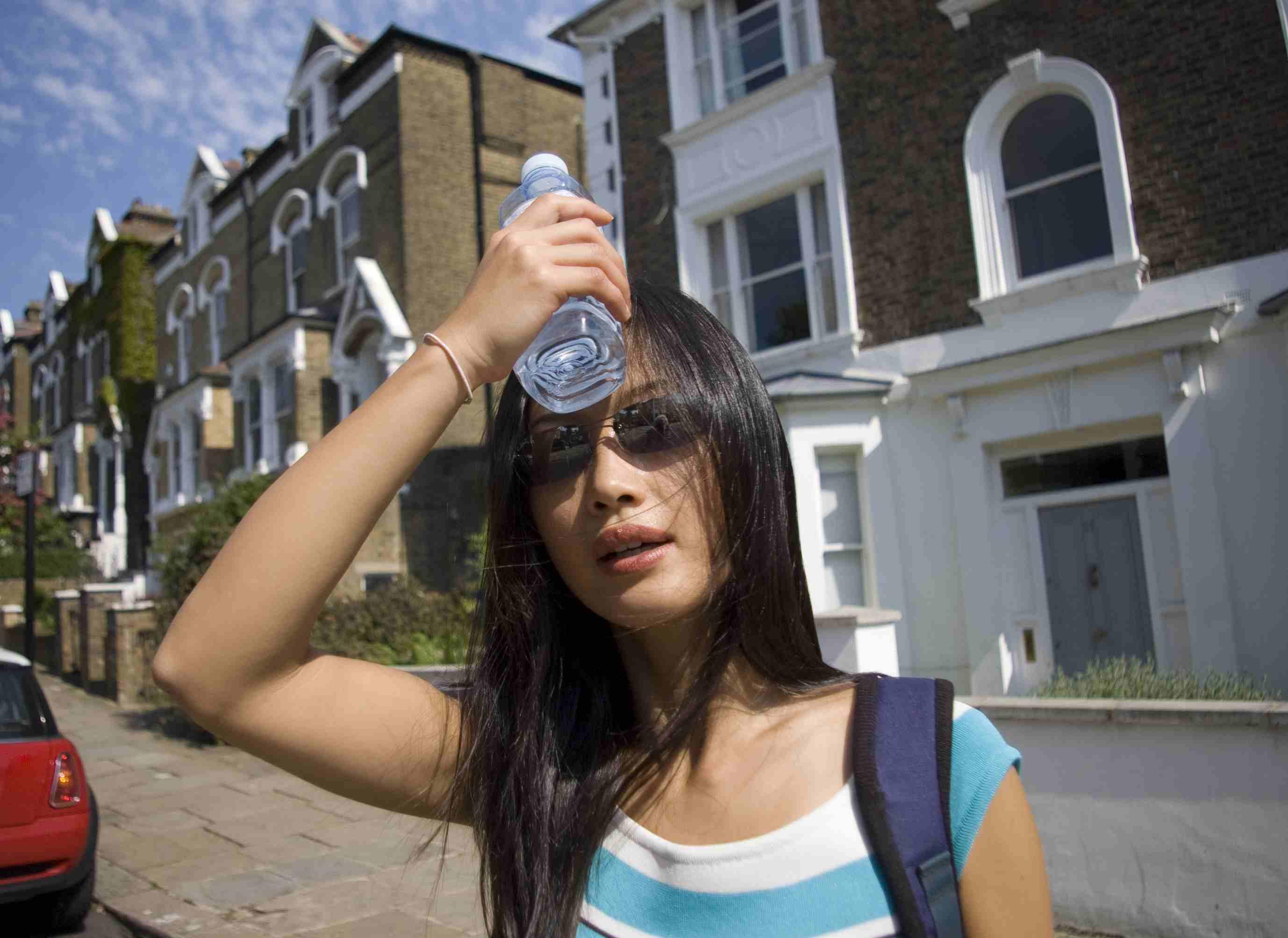 Mujer de pie en la calle poniendo una botella de agua fría en la cabeza