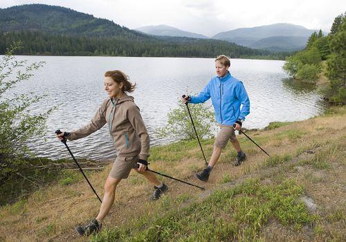 man and woman using walking poles to talk around lake