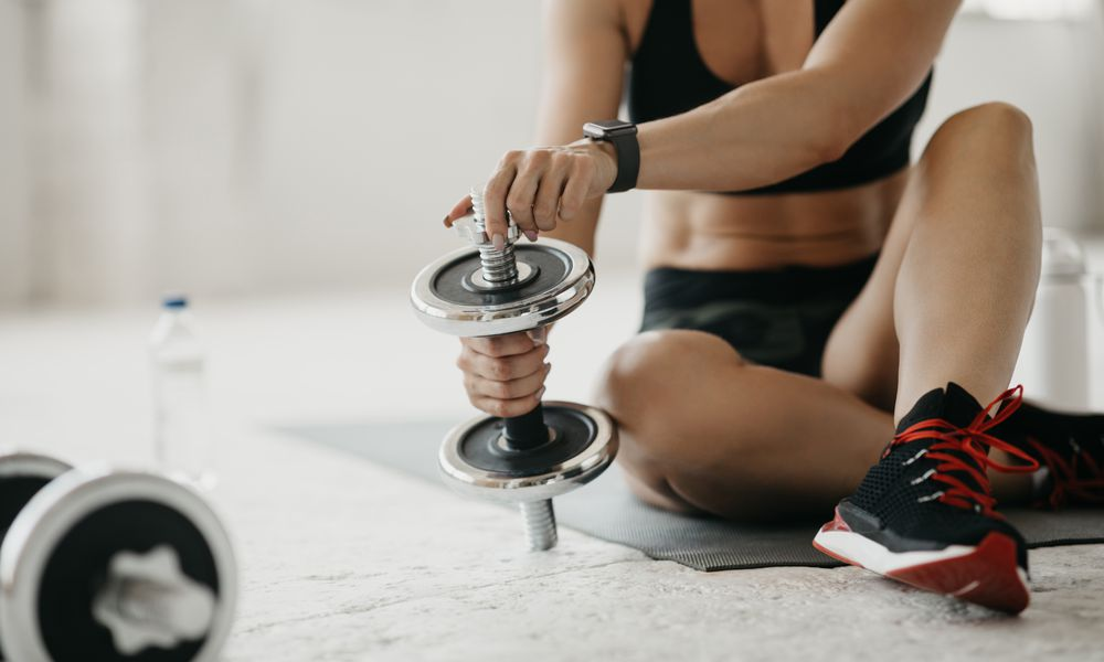 woman adding plates to adjustable dumbbells