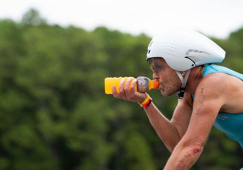 An athlete drinks Gatorade while cycling