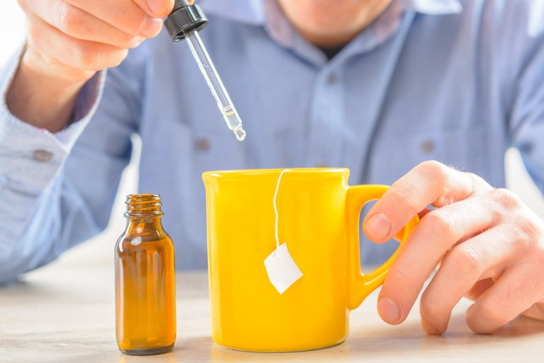 Man adding liquid sweetener to tea