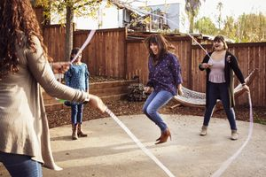 Laughing woman performing double dutch jump rope in backyard