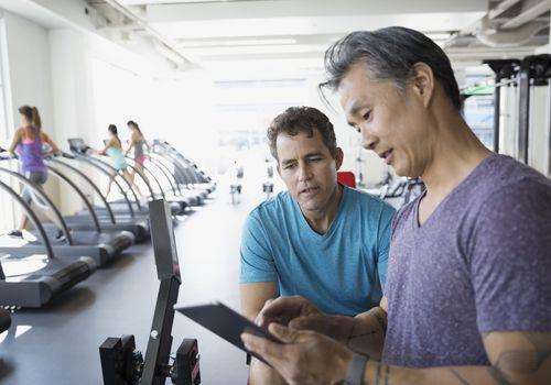 Entrenador personal tableta digital hablando con hombre gimnasio