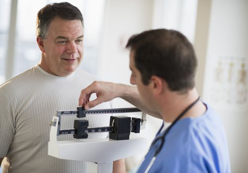 Doctor assisting male patient on weighing scales in hospital