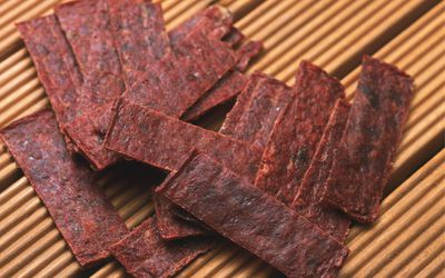 Closed Up Image of Several Slices of Beef Jerky on a Wooden Surface, High Angle View