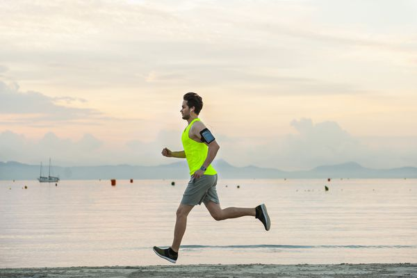 Side view of man jogging on beach