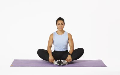 Woman sitting on yoga mat doing butterfly stretch
