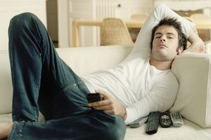 Man relaxing on sofa holding remote controls
