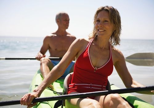 Senior couple in kayak smiling, close-up (focus on woman)