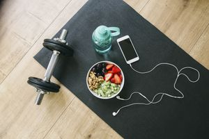 Dumbbell, drinking bottle, fruit bowl and smartphone with earphones