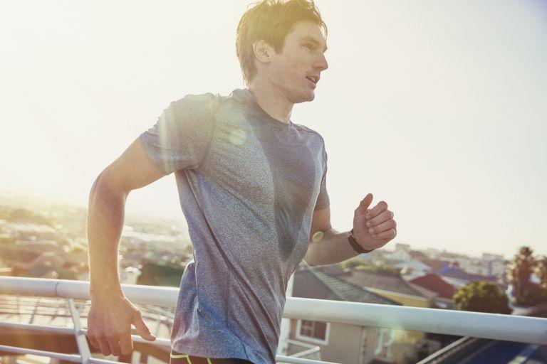 Sweaty male runner running on sunny urban footbridge at sunrise