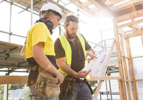 Contratistas que miran planos en una obra de construcción