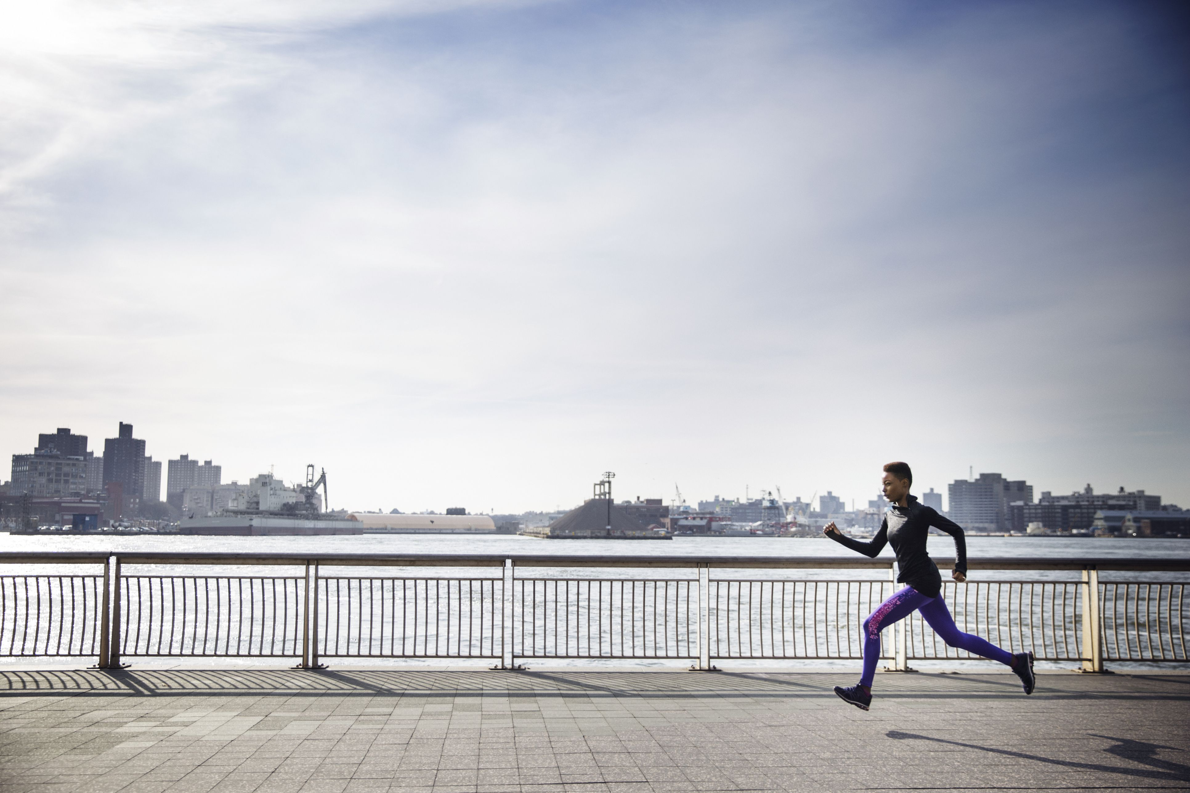 7f064ba2ab Side view of determined female athlete running on footpath by river against  sky