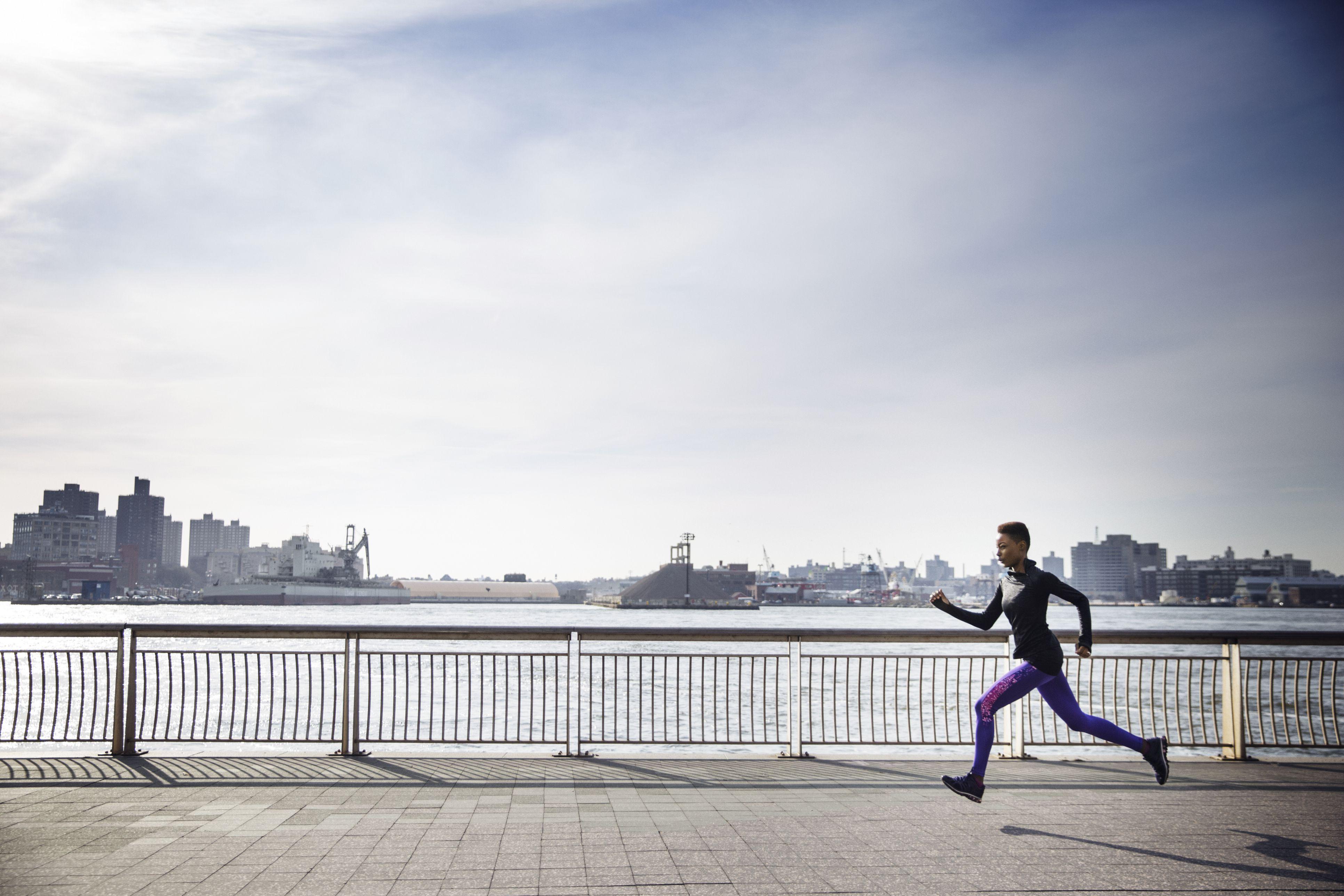 Vista lateral de la atleta femenina determinada que se ejecuta en la acera por el río contra el cielo