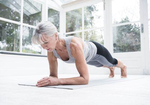 Senior mujer haciendo una tabla sobre una estera de yoga