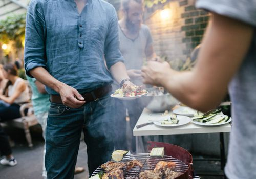 Person filling their plate at a barbecue