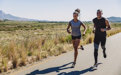 two sporty young people running out on a country road
