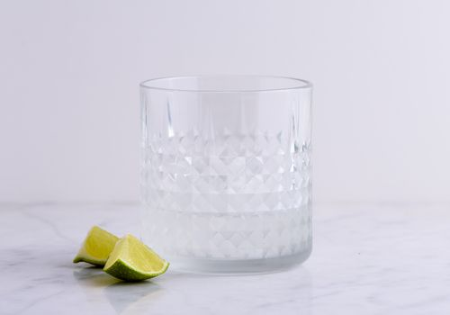 Tequila in glass next to lime wedges