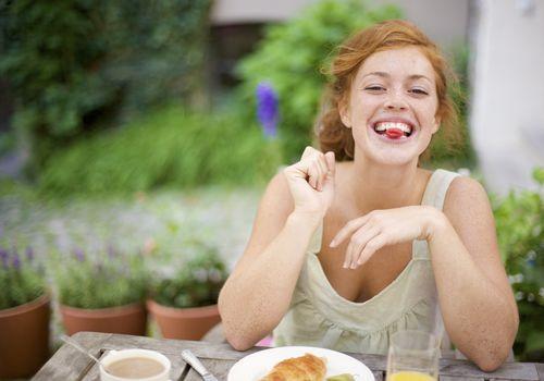 smiling woman eating breakfast