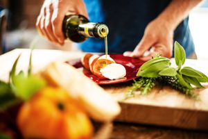 woman pouring olive oil on tomatoes and mozzarella