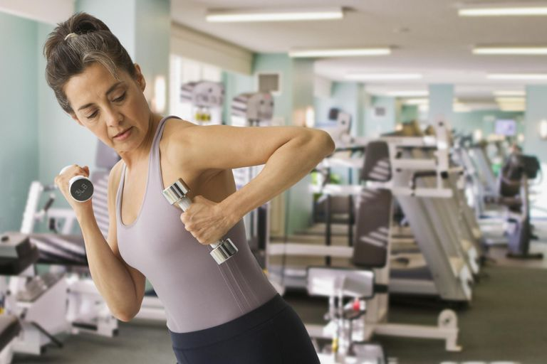woman using hand weights in health club