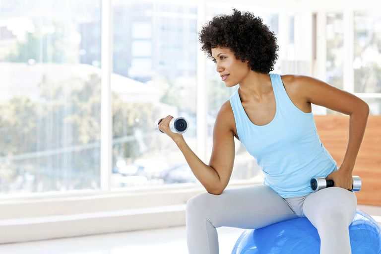 woman exercising with dumbbells while sitting on fitness ball. Horizontal shot.