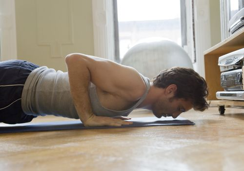 man doing push ups in living room