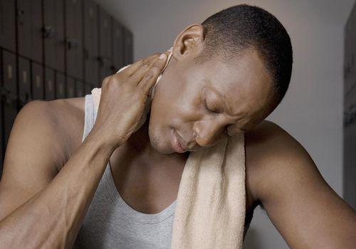 hombre frotando dolor siguiente en el vestuario
