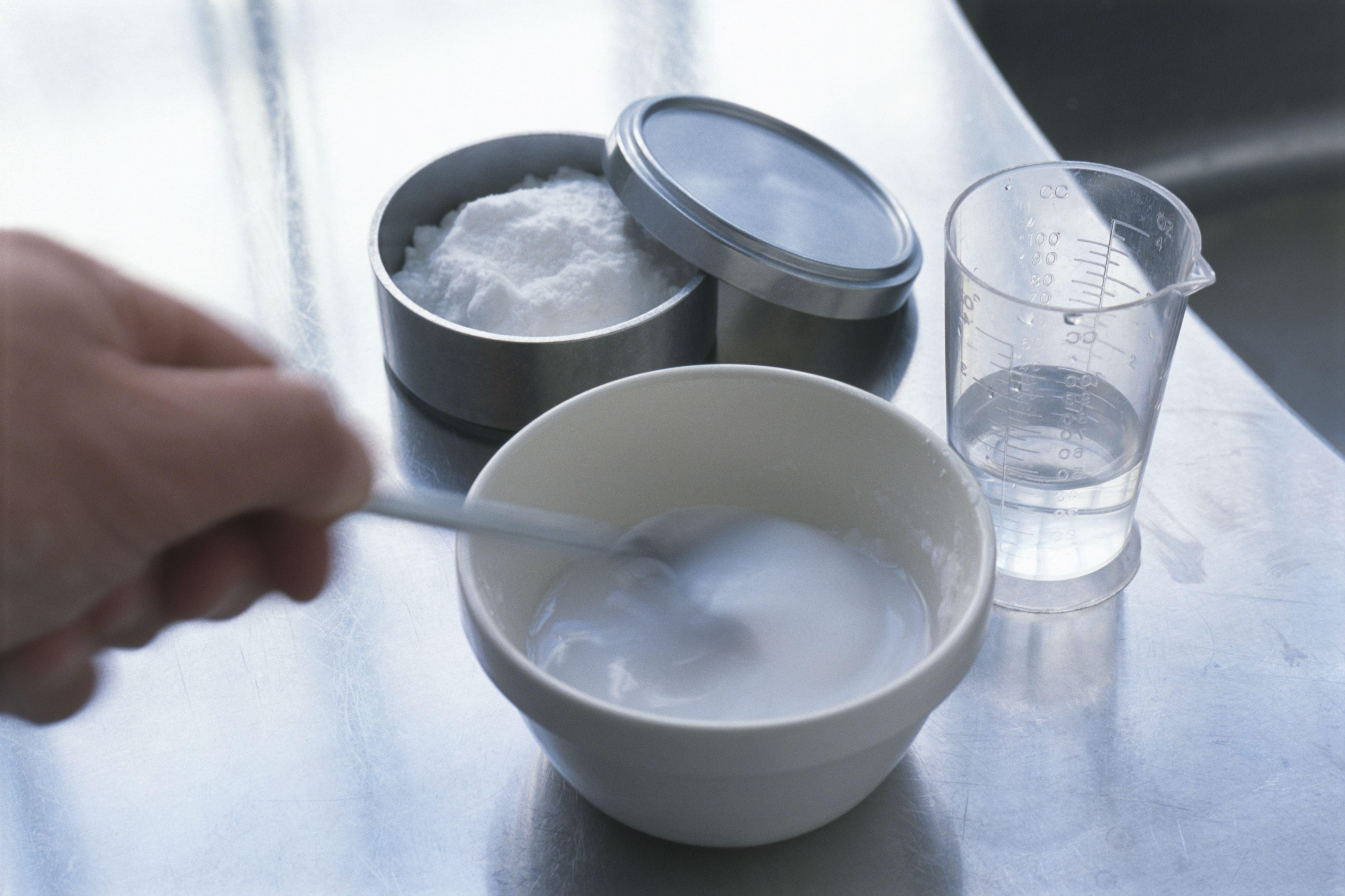 Hacer pasta de bicarbonato de sodio, mezclar el polvo con agua en un tazón, close-up