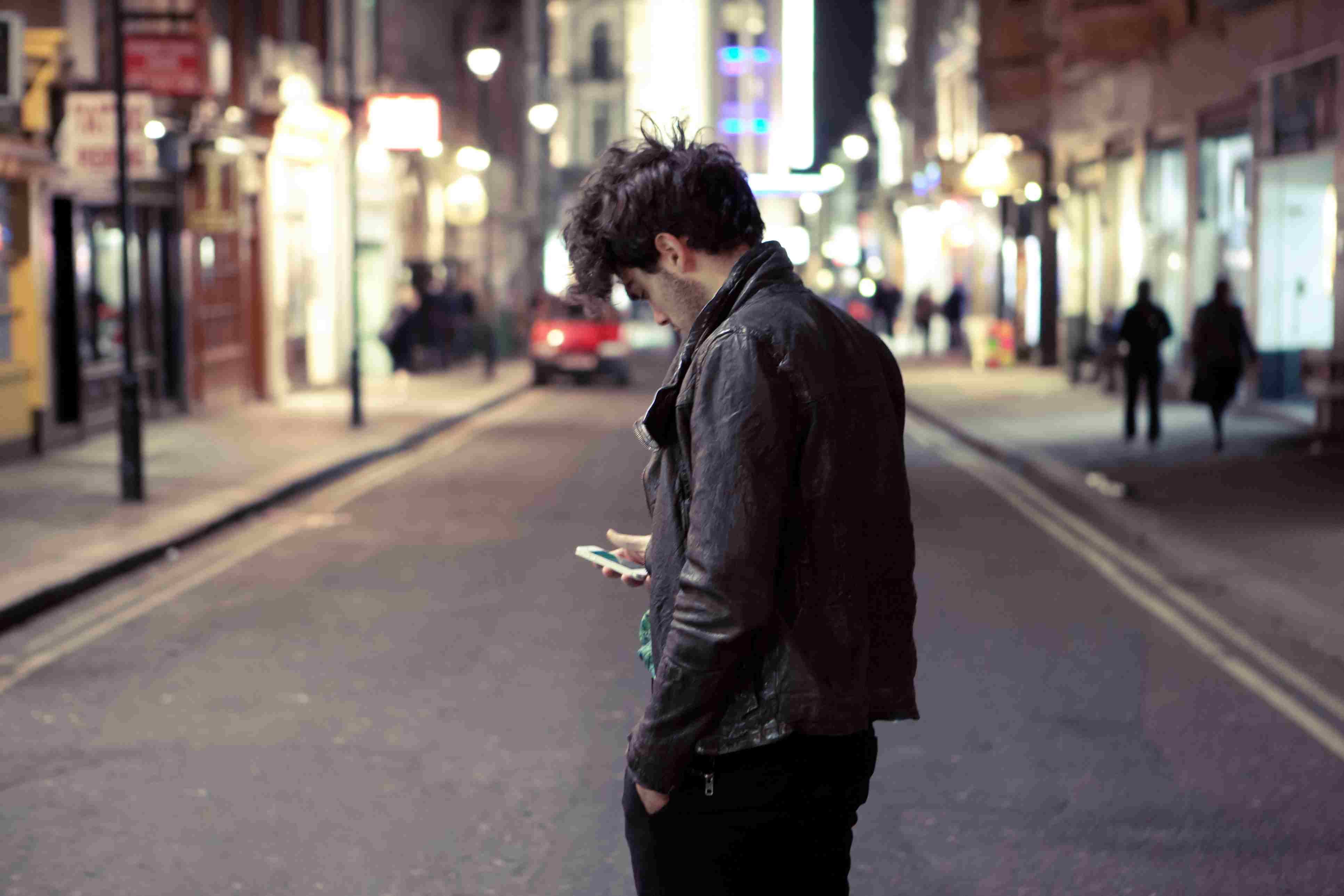 Man looking at his cell phone in the middle of the street