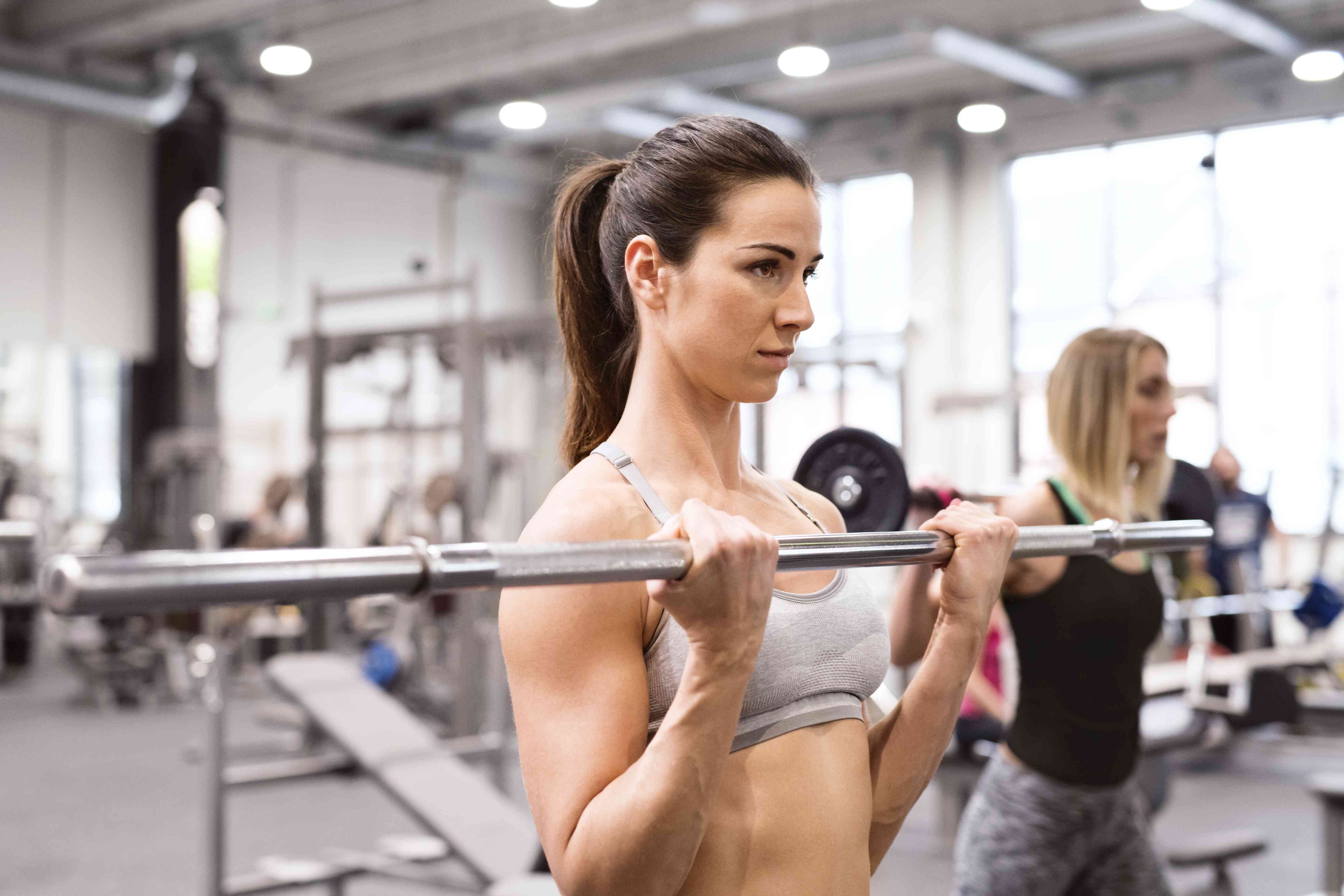 Young woman lifting weights in gym