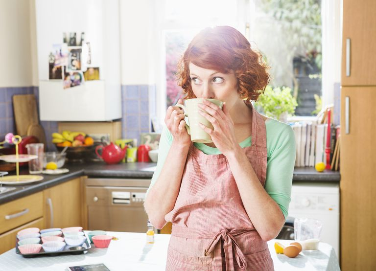 Red-headed woman having a cup of tea in kitchen