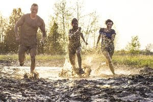 Three young adult athletes in mud race