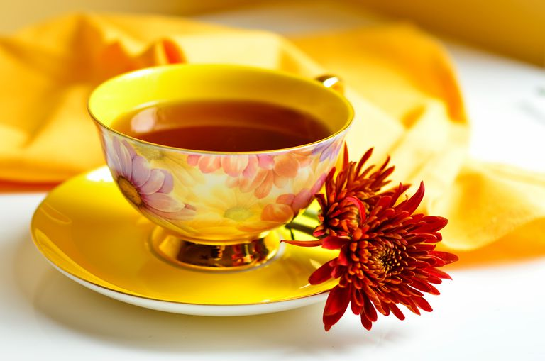Cup of tea and red chrysanthemum