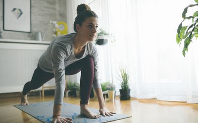 Young woman practicing iyengar yoga at home in her living room