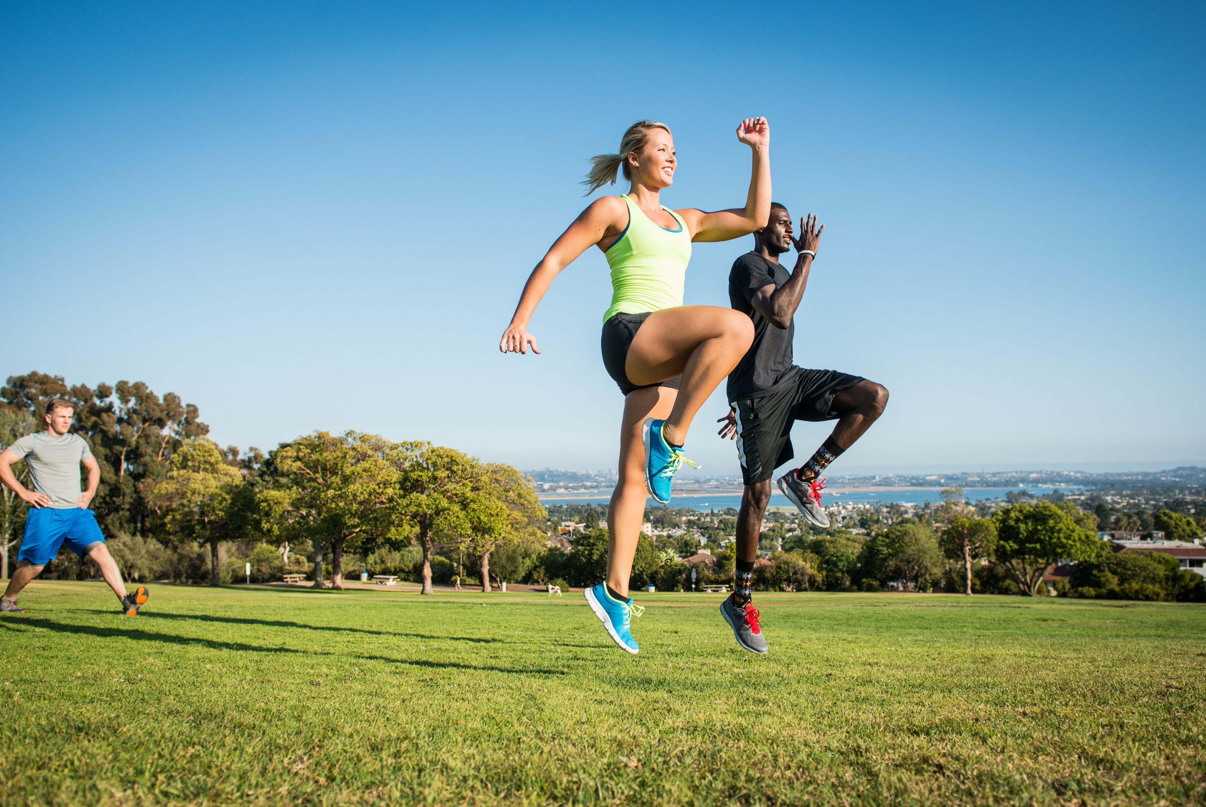 man and woman jumping during workout