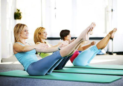 Mujeres haciendo ejercicios de Pilates sobre una estera de ejercicio.
