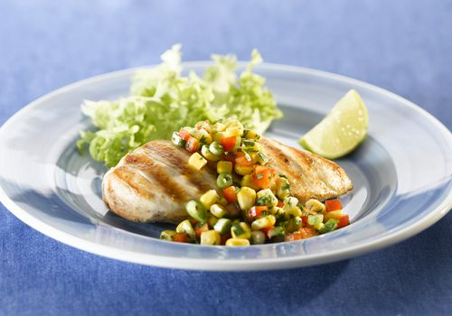 Grilled chicken breast with sweetcorn salsa and slice of lemon on plate, close-up