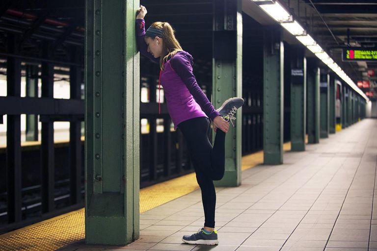 Runner stretching her quads on a subway platform