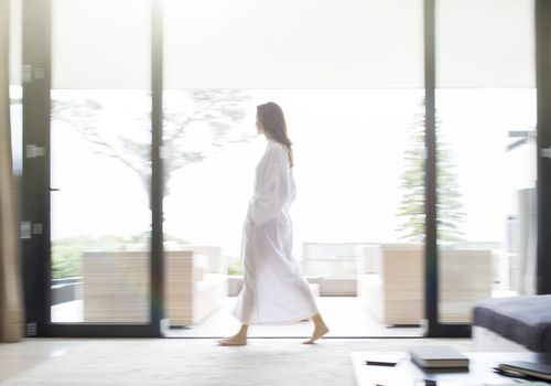 Woman in bathrobe walking through living room