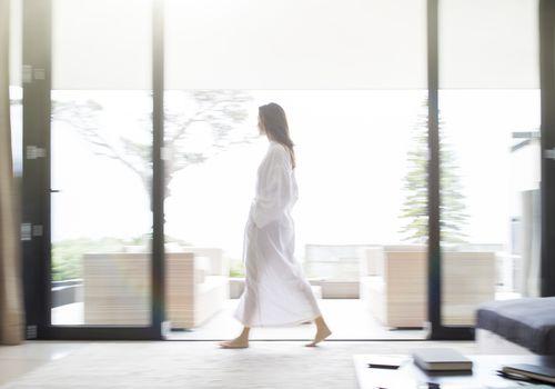 Mujer en bata de baño caminando por la sala de estar