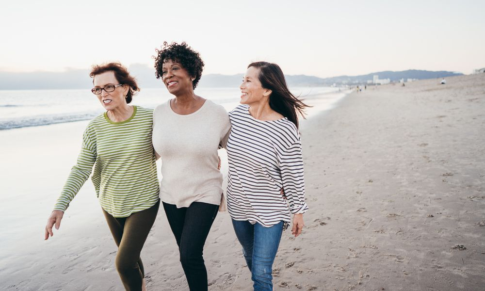 Three middle aged women of different races smiling and walking on the beach together.