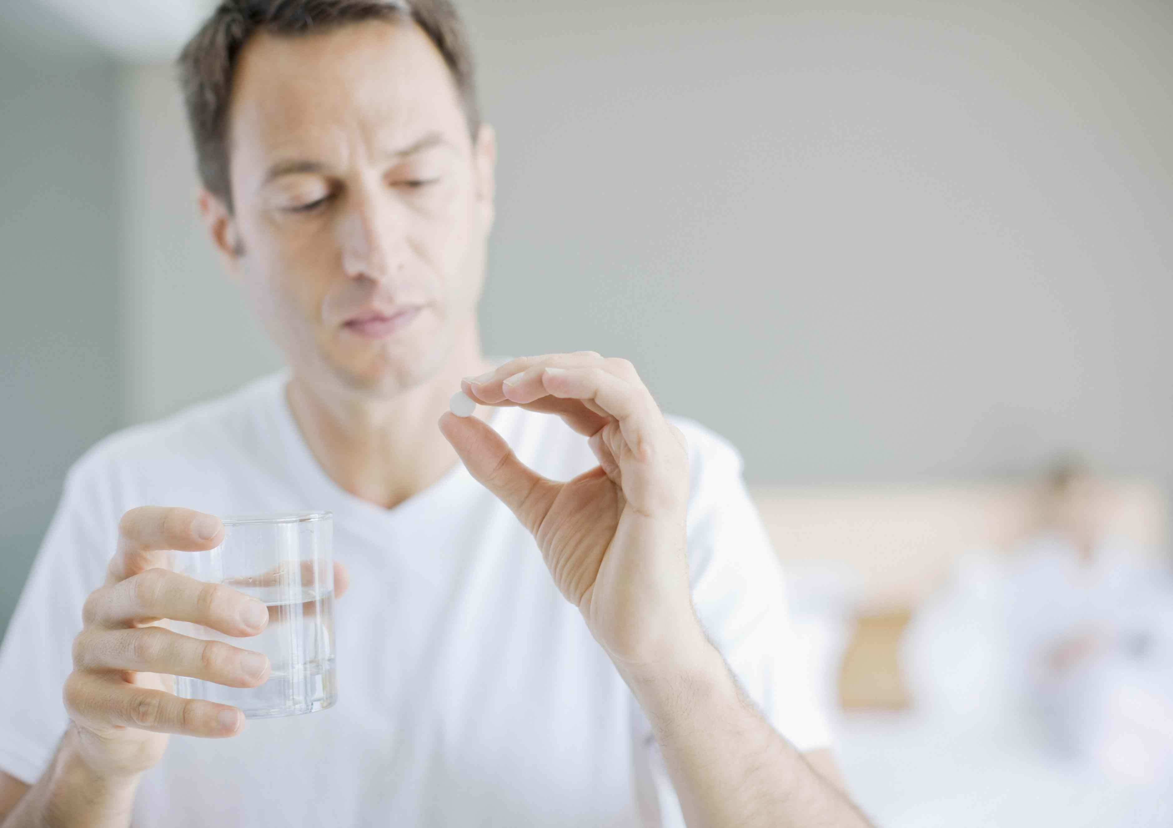 Man holding a pill and a glass of water
