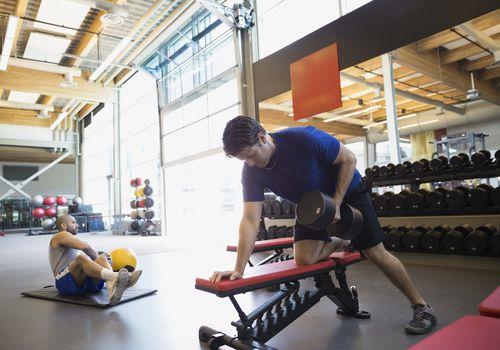Dos hombres trabajando en el gimnasio