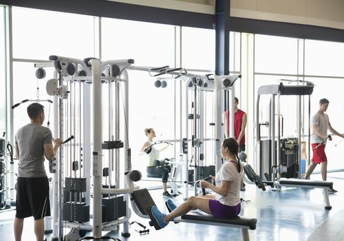 People using weight machines in fitness center