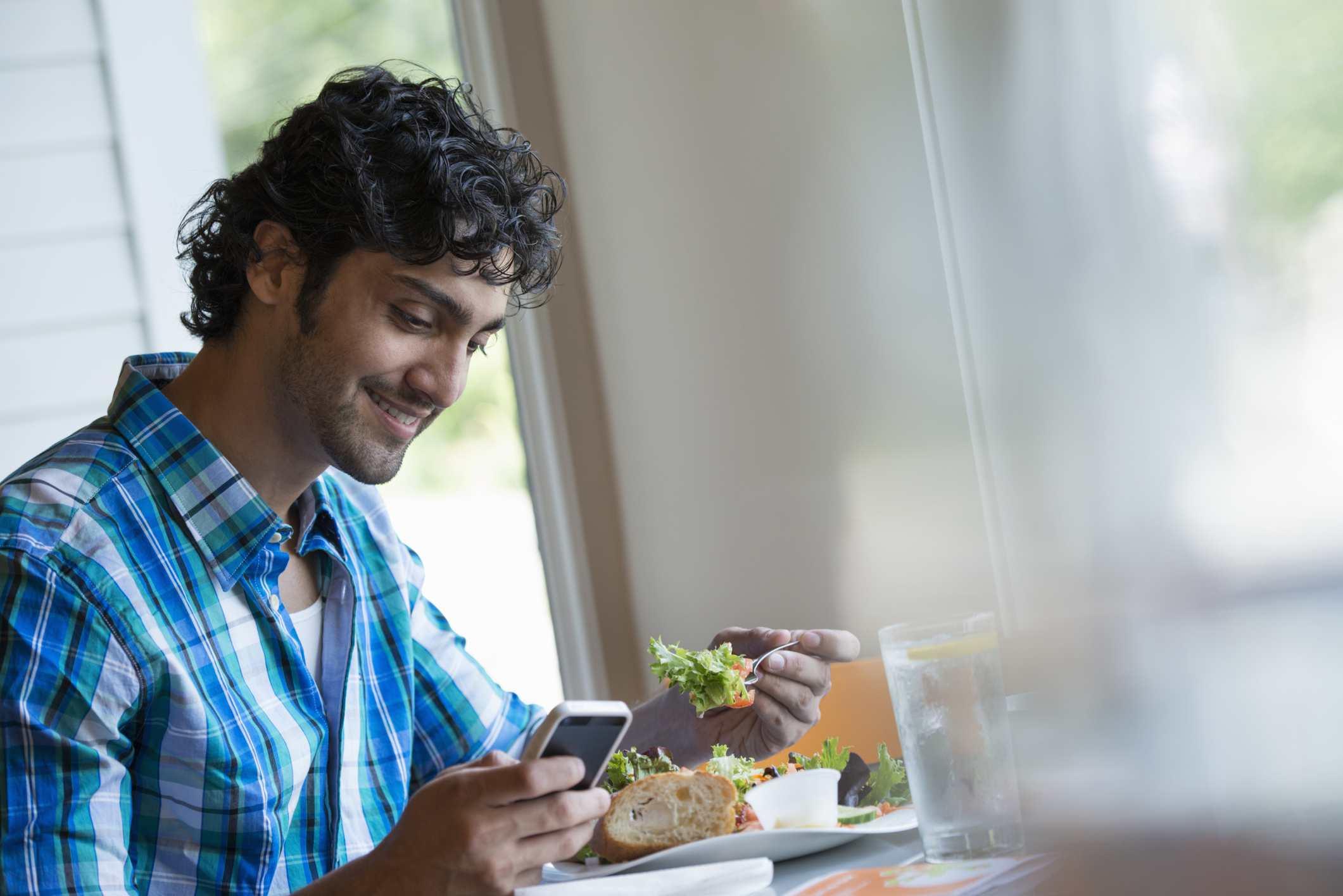Hombre universitario comiendo y usando teléfono celular.