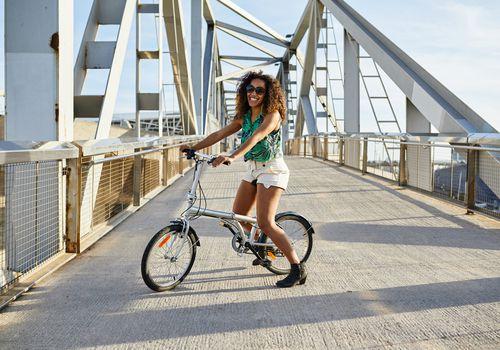 Mujer montando bicicleta en ruta de puente