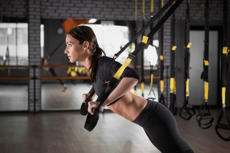 Fitness woman training with fitness straps