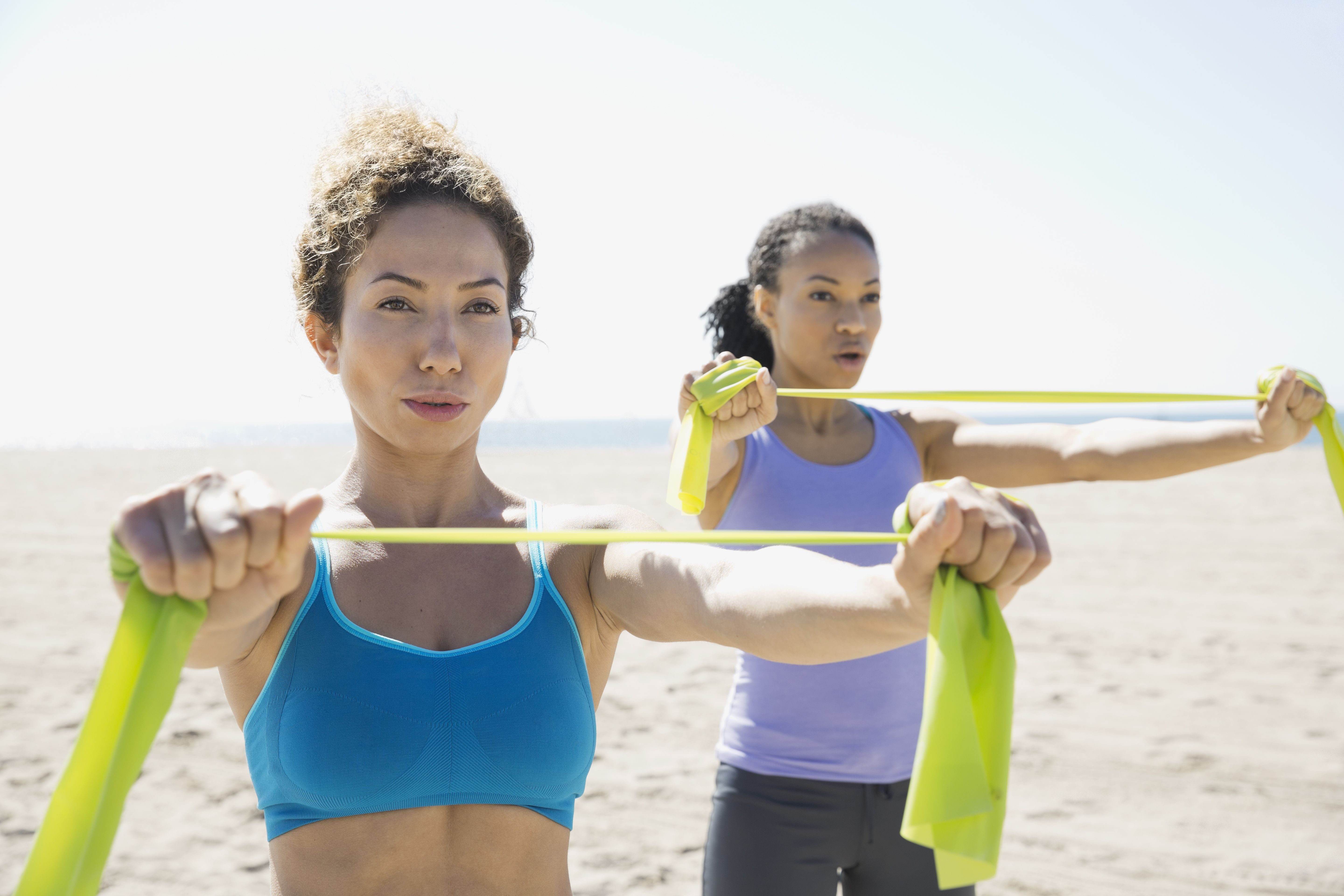 Women exercising with resistance band on beach